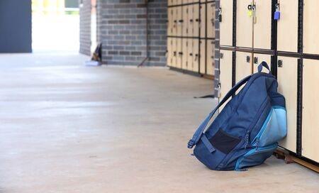 single blue school backpack outside a classroom with lockers in the background