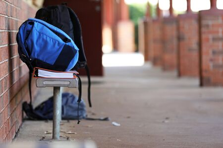 bright blue high school back pack school bag on a chair outside a classroom