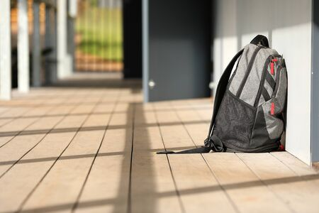 Black school bag duffle bag backpack outside a classroom on a high school education site. Zdjęcie Seryjne