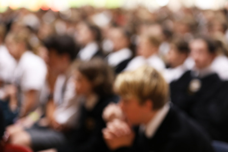 Students in uniform sitting listening attentively at high school assembly facing the same direction. heavy blurred for anonymity and background effect. Educational eduction teacher pedagogy concept. audience crowd shot out of focus