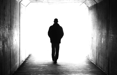 Black and white male person figure in a tunnel walking heading towards a bright light. Concept of death, dying, afterlife, moving on, transition, heaven, suicide, depression, mental health isssues.
