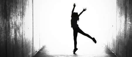 digitally enhanced - altered illustration like, black and white silhouette of a single solo girl dancing jumping by herself in a tunnel