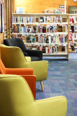 Soft inviting contemporary modern sofa arm chairs inside a high school library with books and shelves in the background, portrait view