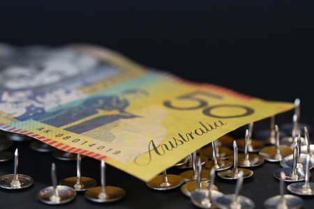 close up extreme shallow depth of field macro shot of australian fifty dollar note supported on sharp thumb tacks or drawing pins. Finance business economy concept. Banco de Imagens