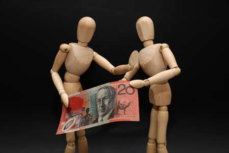 A pair of wooden mannequins talking discussing fighting arguing over financial strain pressure hardship. Struggling over a twenty dollar note. Domestic stress personal money finances debt concept.