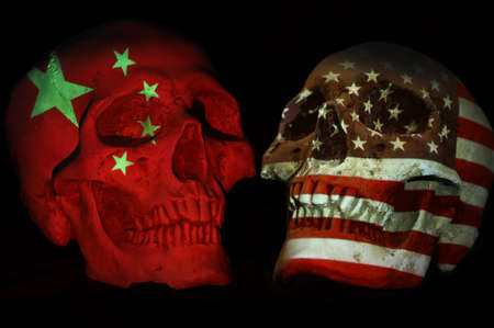 Opposing skulls with national emblem or flag patriotic symbol projected over. Isolated black background. Political tensions concept