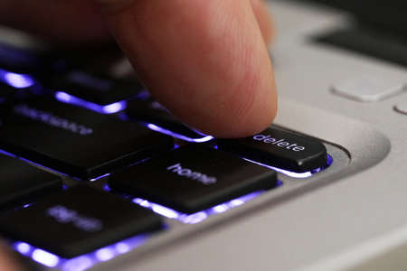 Extreme close up of a finger pressing the delete tab on a computer keyboard. Blue back lit computer laptop keys with a digit pushing the delete button.