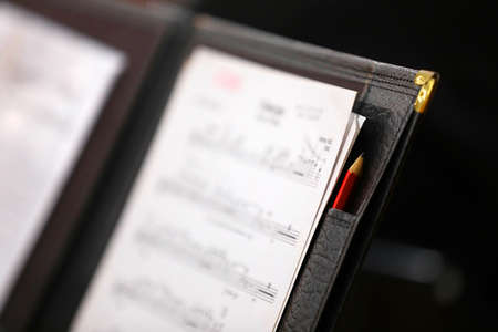 Black leather music score sheet folder with red pencil and brass corner. Close up shallow depth of field. Landscape orientation Banque d'images