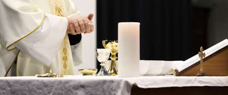Close up image of a parishoners hands clasped receiving the bread during holy communion from a catholic priest at Mass.