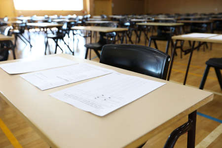 View of large exam room hall and examination desks tables lined up in rows ready for students at a high school to come and sit their exams tests papers.