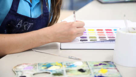 Students working in their visual art process diaries exploring experimenting with colour theory. Painting in workbooks. Creative arts education concept.