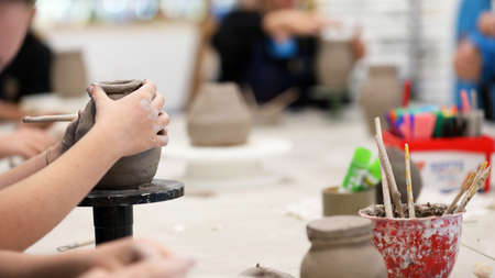 students working with clay getting their hands dirty. Visual art class showing hands on a coil pot with clay tols and desk in background. Art education in schools. Creativity and artistry at work. Teaching ceramics