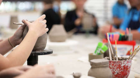 students working with clay getting their hands dirty. Visual art class showing hands on a coil pot with clay tools and desk in background. Art education in schools. Creativity and artistry at work. Teaching ceramics