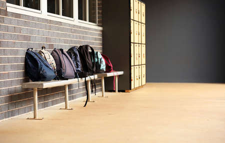Portrait orientation of pile of school bags backpacks or duffle bags. Outside a classroom in an educational facilty. School yard and buildings.