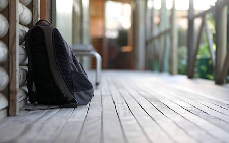 Low angle shallow depth of field shot of a solitary black school bag or backpack outside a classroom. Education focus Banco de Imagens