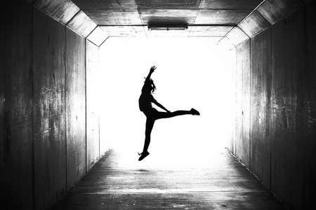 Digitally altered illustration style photograph of a single solo girl jumping with a dance move in a dark city urban tunnel. Gymnastic dancing fitness energy style illustration