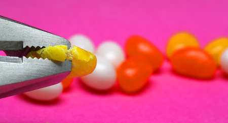 A close up of a stainless steel plier head crushing a yellow jelly bean lolly or candy. Bright pink purple blurred backkground with multiple orange and white lollies candies.