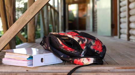A school bag leaning up against a ring-binder folder filled with lesson notes and paper outside a classroom building at a high school educational facility. Exam study revision success concept Banco de Imagens