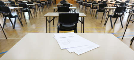 Students eye view of a math mathematics exam examination paper set up on a desk table. Empty Secondary High School hall ready for major final exams to be sat.