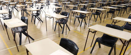 A large high school hall or room set up ready for an end of year final exam to be sat by students. examination paper sitting on the edge of a desk or table. Banco de Imagens