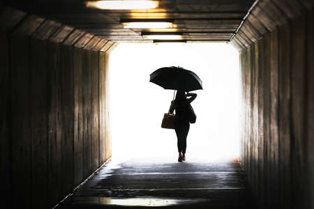 Highly saturated silhouette of a confident woman holding an umbrella exiting a tunnel. Wet weather working city chic lifestyle. Weather forecast, rain and showers. Leaving arriving confidence concept