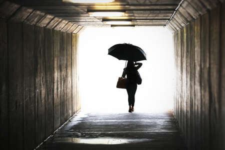Highly saturated silhouette of a confident woman holding an umbrella emerging from a tunnel. Wet weather working city chic lifestyle. Weather forecast, rain showers Leaving arriving confidence concept