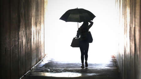 Illustration style enhanced silhouette of a confident woman holding an umbrella emerging from a tunnel. Wet weather working city chic lifestyle. Weather forecast rain showers Leaving arriving confidence concept Banco de Imagens