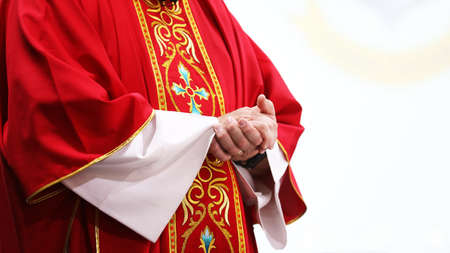 close up of a catholic priest during mass in a church wearing a bright red gold patterned vestment or robe. Standing with hands clasped, white background. Banco de Imagens