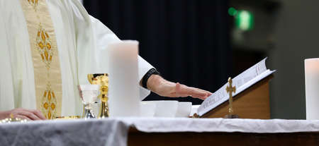 detail of a catholic priest serving mass at a liturgy. Images shows various symbols of catholicism, religious values and objects. Religion religious theme and concept with variety of symbolic church references.