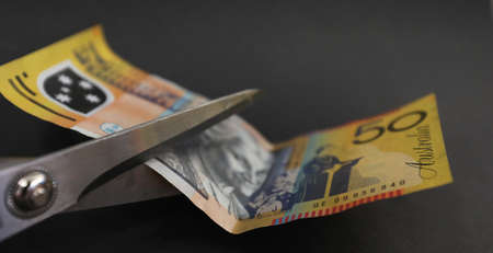 Australian 50 fifty dollar note about to be cut with scissors. tax cut saving spending cuts divorce and separation settllement concept. Budget stress or pressure