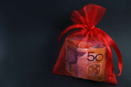 A prettty red glittery bag holding a wad of cash or currency. 50 fifty dollar note clearly visable through bag. Gift, financial assistance, support and bonus concept. Lottery winnings, fairytail result from business success.