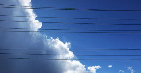 Interesting alternative creative view looking up through power lines to white fluffy clouds building up into a tropical thunder storm. Intense deep blue sky and artistic impression from below.