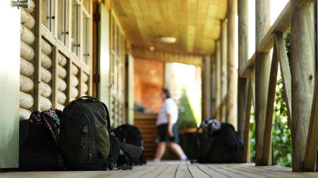Image of piled up school bags outside a log cabin style classroom at high school. Blurred in the background a student walks past. Education theme