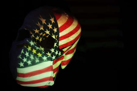 The American stars and stripes flag projected over a skull wearing a breathing face mask. Corona virus covid 19 global pandemic social distancing measures concept. Banco de Imagens