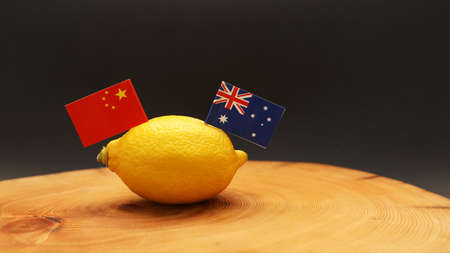 Australian and Chinese flags poking out of a lemon on a chopping block representing the strained soured relationship and trade war being waged between the two countries.