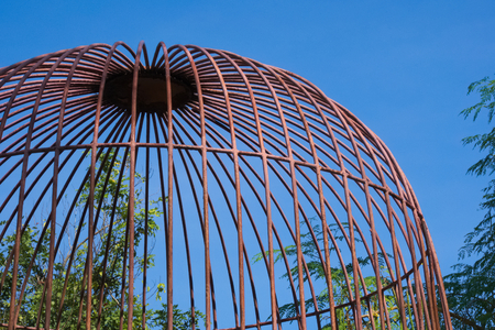 Rustic domed cage protecting gardening supplies in a beautiful garden park in Bangkok, Thailand.