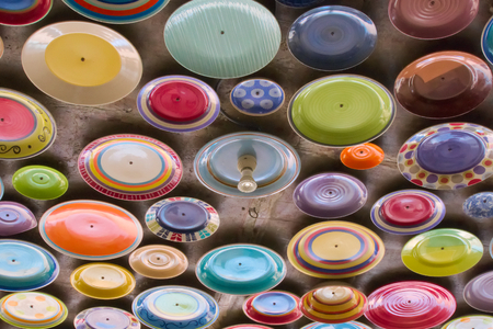 Colorful and beautiful array of plates, positioned on the ceiling of a lovely outdoor restaurant. Stock Photo