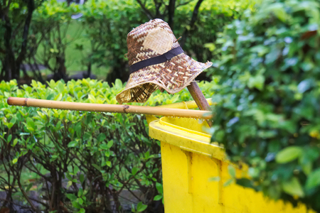 A straw hat, simple Thai broom and a yellow garbage bin; all abandoned quickly because of a sudden summer rainstorm, the remnants of the Asian gardener, who smartly got undercover, quickly. Stock Photo