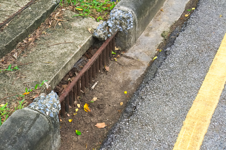 A steel curb drainage, that has eroded beyond repair, on a street, in the country of Thailand, which sees heavy rainy seasons.