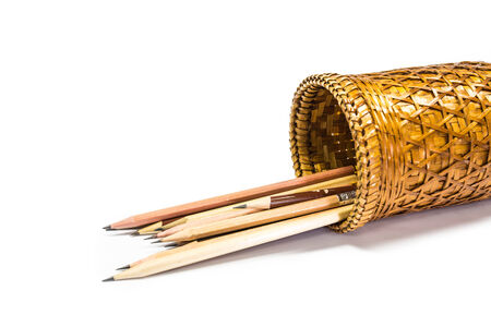Woven basket and pencil on a white