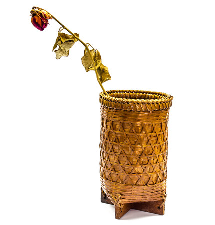 A dried rose  in rattan basket on a white background. photo