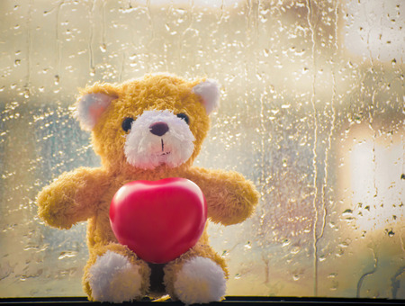 valentine s day teddy bear: teddy Bear with Heart concept valentine background with water drops on the glass, vintage retro tone.