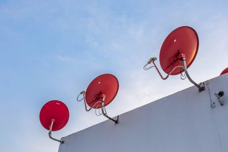 dish disk: Three Red parabolic antenna on a background of blue sky