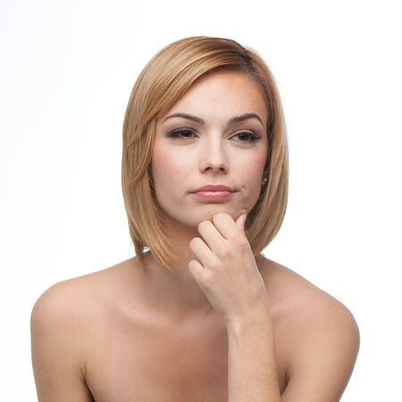 a portrait of a young, blonde woman, holding her chin with one hand, with a wondering expression on her face photo