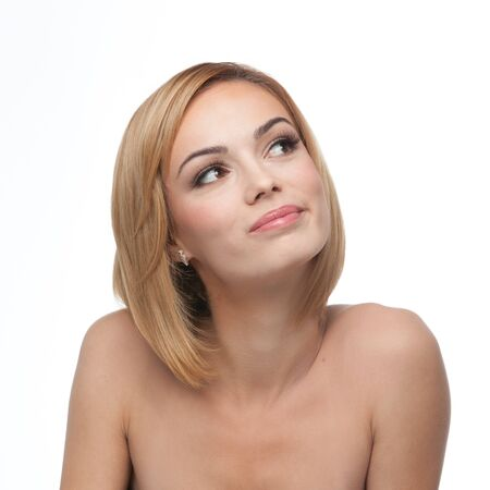 a portrait of a young, blonde woman, looking up, to the right, with a happy, daydream expression photo