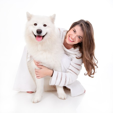 a studio image of a young woman, dressed in white, with her white dog, huging it, both posing, looking happy and smiling photo