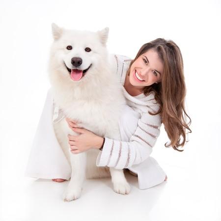 frau mit hund: ein Studio-Bild einer jungen Frau, wei� gekleidet, mit ihrem wei�en Hund, Huging es, beide posiert, freudig und l�chelnd Lizenzfreie Bilder