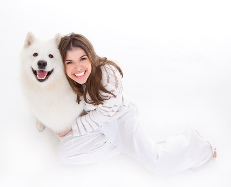 a studio image of a young woman, dressed in white, with her white dog, huging it, both posing, looking up, being happy and smiling.
