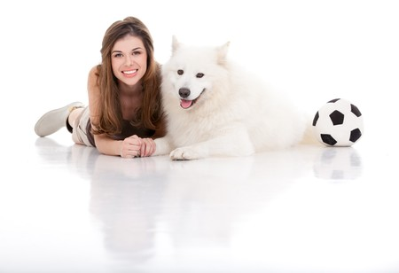 a studio image of a young woman with a white dog, both posing by sitting  their belly, holding hands, smiling, with a football on their side. photo