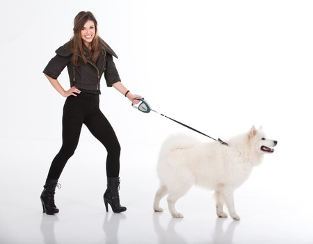 side pose: a studio image of a young woman, dressed in black, smiling, walking her white dog. they are both viewed from a side, with her looking to the camera and the dog in front of him. Stock Photo
